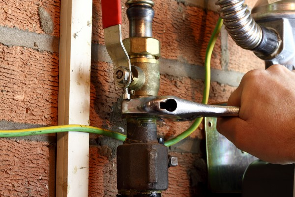 Plumber connecting a copper gas pipe in a home