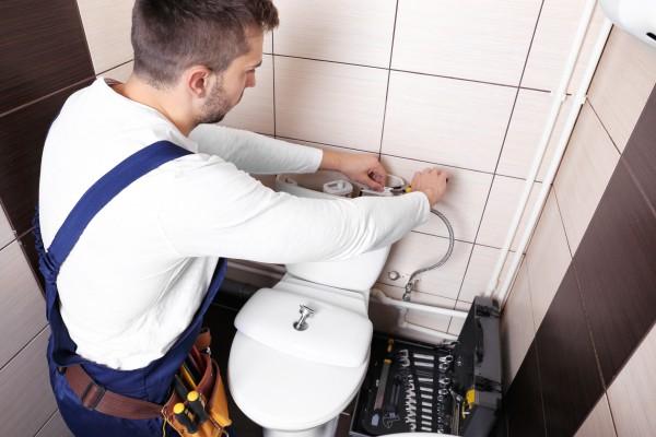 Plumber fixing a toilet leak